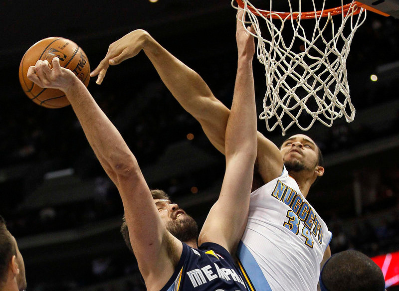 . Memphis Grizzlies center Marc Gasol (L) has a shot blocked by Denver Nuggets center JaVale McGee in the first quarter of their NBA basketball game in Denver December 14, 2012.   REUTERS/Rick Wilking
