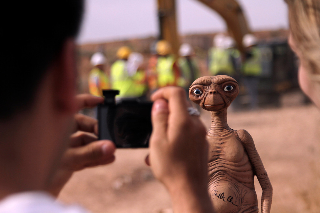 . A man takes a photo of an E.T. doll in Alamogordo, N.M, Saturday, April 26, 2014. Producers of a documentary dug in an southeastern New Mexico landfill in search of millions of cartridges of the Atari \'E.T. the Extra-Terrestrial\' game that has been called the worst game in the history of video gaming and were buried there in 1983. (AP Photo/Juan Carlos Llorca)