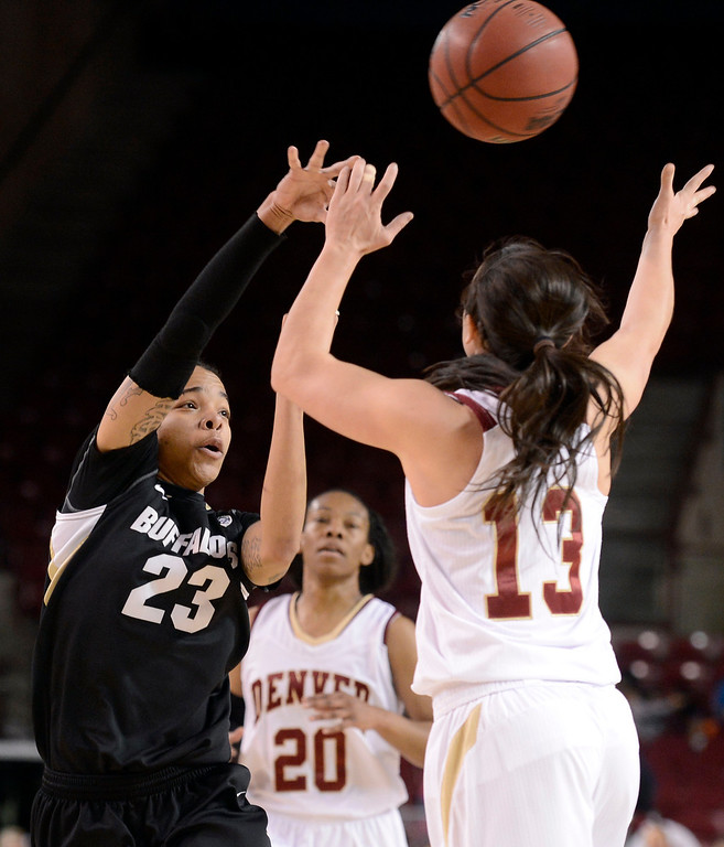 . University of Colorado\'s Chucky Jeffery passes the ball over the hands of Emiko Smith during a games against the University of Denver on Tuesday, Dec. 11, at the Magnus Arena on the DU campus in Denver.  (Jeremy Papasso/Daily Camera)