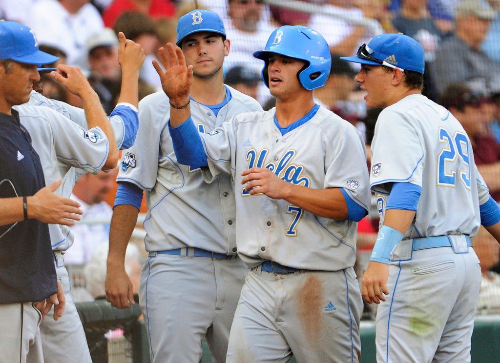 . UCLA\'s Kevin Kramer (7) is greeted by teammates, including Ty Moore, right, after he scored against Mississippi State on a single by Pat Valaika in the first inning of Game 1 of the NCAA College World Series best-of-three finals, Monday, June 24, 2013, in Omaha, Neb. (AP Photo/Francis Gardler)