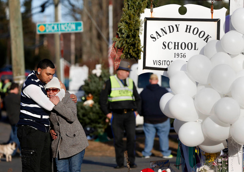 Description of . People grieve next to a makeshift memorial of flowers and balloons next to the Sandy Hook Elementary school sign in Sandy Hook, Connecticut December 15, 2012. Investigators assembled
