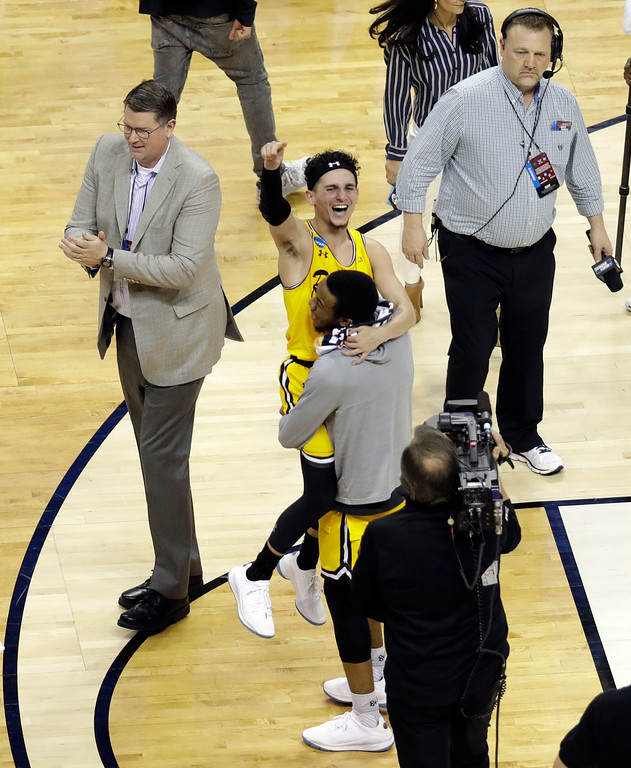 . UMBC\'s K.J. Maura, center, celebrates with a teammate after UMBC defeated Virginia 74-54 in a first-round game in the NCAA men\'s college basketball tournament in Charlotte, N.C., Friday, March 16, 2018. (AP Photo/Chuck Burton)