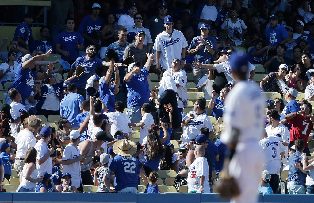 . Los Angeles Dodgers shortstop Dee Gordon watches as fans grab for San Francisco Giants\' Brett Pill\'s home run ball during eighth inning of a baseball in Los Angeles, Sunday, Sept. 15, 2013. (AP Photo/Chris Carlson)