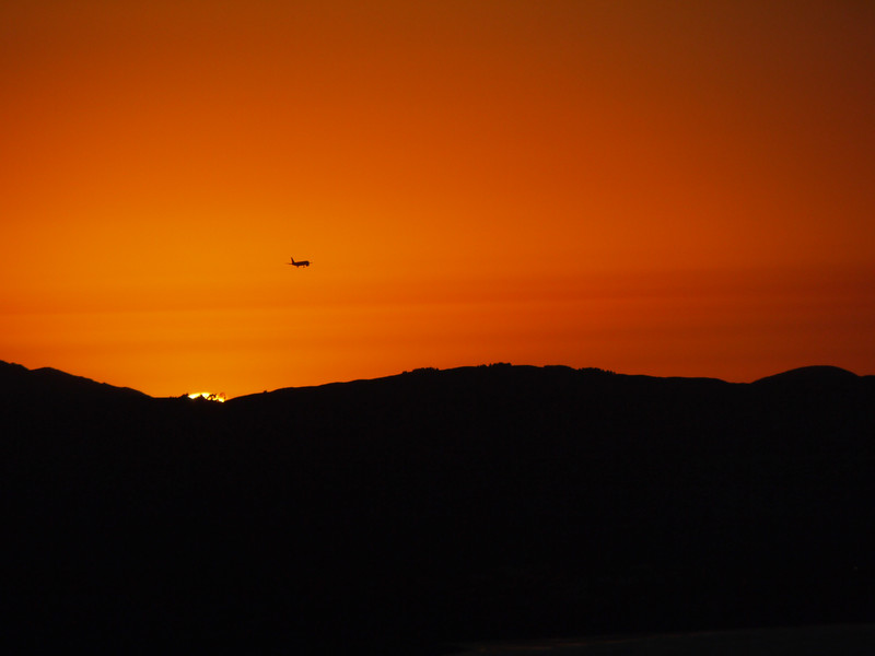 A plane heading North at Sunset over the bay.