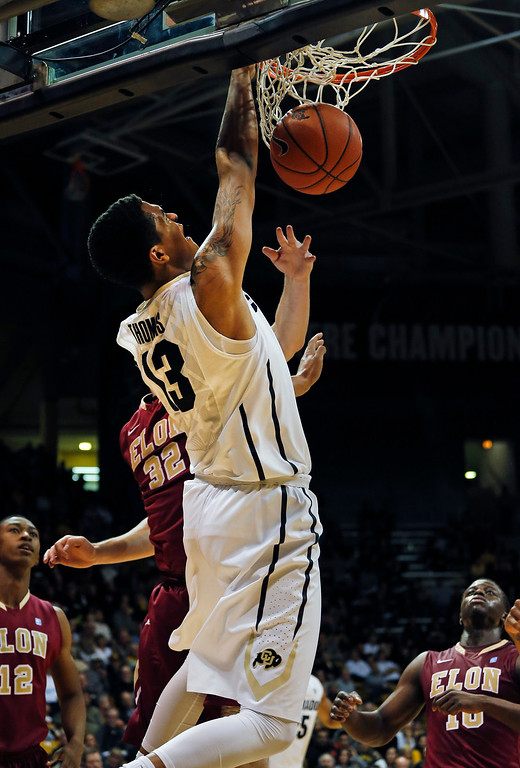 . Colorado\'s Dustin Thomas dunks during the first half of an NCAA college basketball game against Elon in Boulder, Colo., Friday, Dec. 13, 2013. (AP Photo/Brennan Linsley)