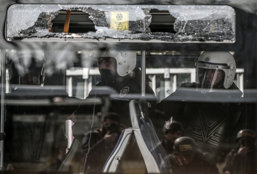. Riot police officers wait in a damaged bus as thousands of people march for Berkin Elvan, a Turkish teenager who was in a coma since being hit on the head by a tear gas canister fired by police during anti-government protests in the summer of 2013, during his funeral in Istanbul, Turkey, Wednesday, March 12, 2014. On Wednesday, thousands converged in front of a house of worship calling for Prime Minister Recep Tayyip Erdogan to resign. (AP Photo/Emrah Gurel)