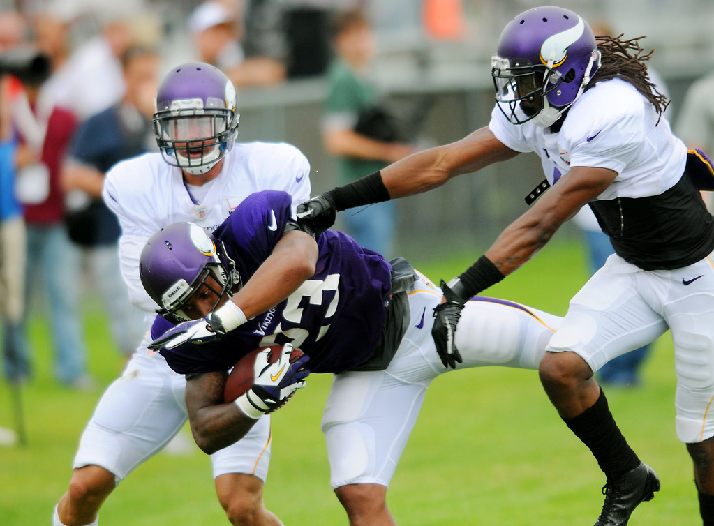 . Andrew Sendejo, left, and Mistral Raymond, right, shove running back Joe Banyard out of bounds during drills.  (Pioneer Press: John Autey)