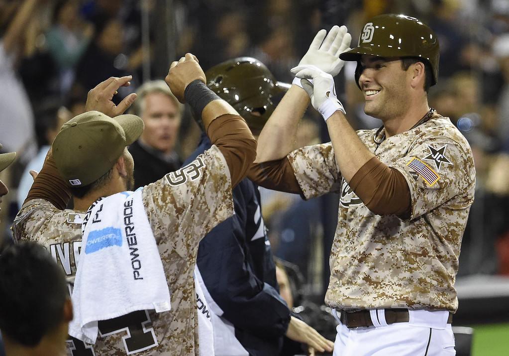 . Seth Smith #12 of the San Diego Padres, right, is congratulated after hitting a solo home run during the eighth inning of a baseball game against the Los Angeles Dodgers on Opening Night at Petco Park on March 30, 2014 in San Diego, California.  (Photo by Denis Poroy/Getty Images)