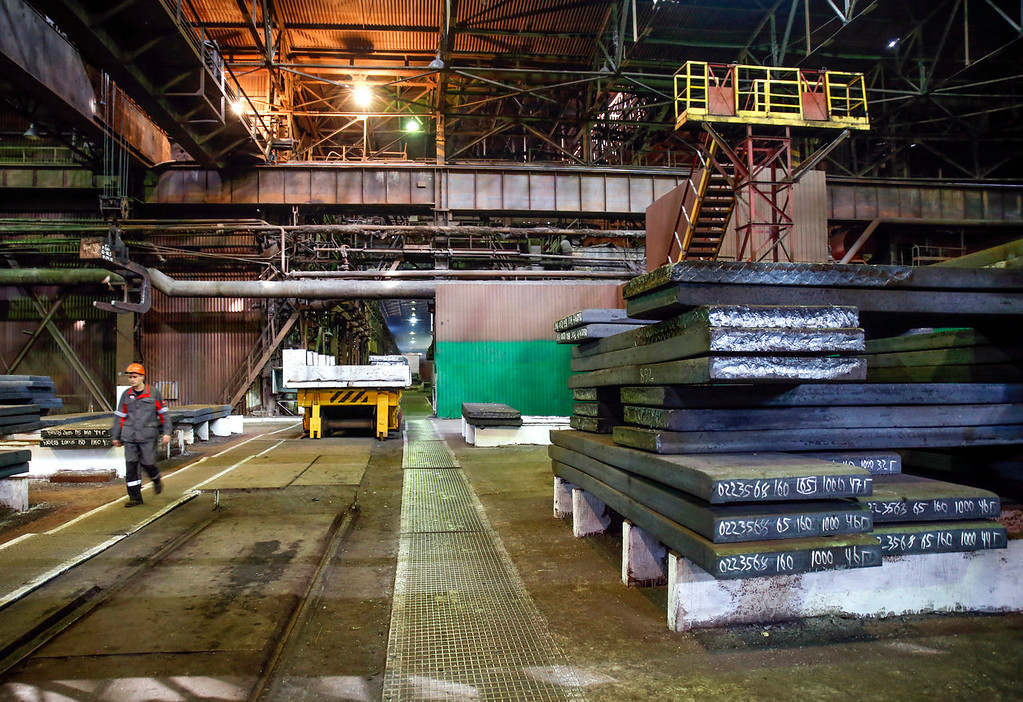 . An employee walks past steel plates marked and coded inside the Zaporizhstal steel plant, owned and operated by Metinvest BV at their site in Zaporizhzhya, Ukraine, on Tuesday, Oct. 15, 2013. Metinvest BV, Ukraine\'s largest steelmaker, last year acquired 49.9% in steelmaker Zaporizhstal a manufacturer of semi-finished steel products, including hot and cold-rolled plates and coils. Photographer: Vincent Mundy/Bloomberg