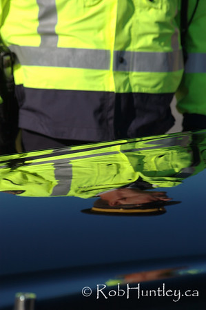Reflection of an RCMP (Royal Canadian Mounted Police) officer in the hood of a black limousine transporting dignitaries to the 2009 Remembrance Day Ceremony in Ottawa, Ontario. © Rob Huntley