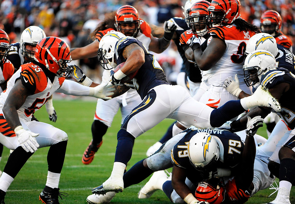 Description of . San Diego Chargers running back Ryan Mathews, center, leaps over two players against the Cincinnati Bengals defense during the second half of an NFL football game, Sunday, Dec. 2, 2012, in San Diego. (AP Photo/Denis Poroy)