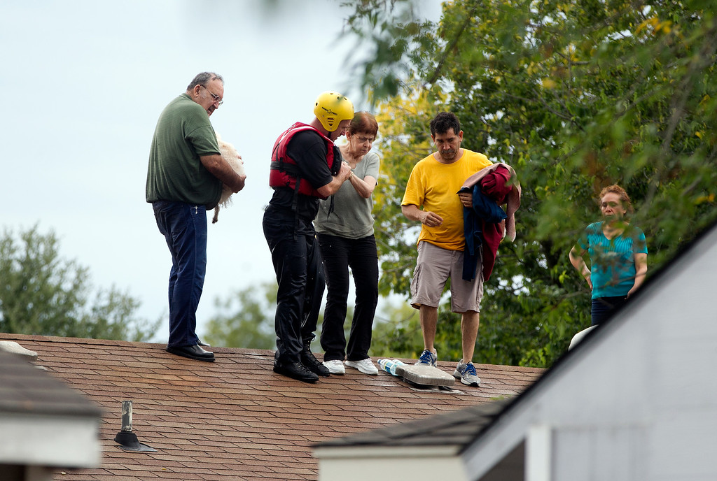 . People are rescued from a home\'s rooftop  in southeast Austin, Texas, on Thursday, Oct. 31, 2013. Heavy overnight rains brought flooding to the area. The National Weather Service said more than a foot of rain fell in Central Texas, including up to 14 inches in Wimberley, since rainstorms began Wednesday.  (AP Photo/The Austin American-Statesman, Deborah Cannon)