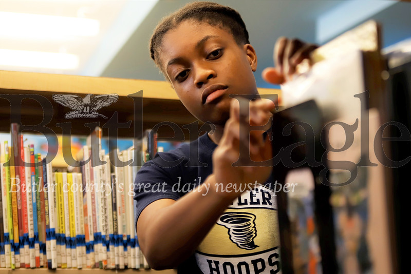 Library intern Sarayne Forbes, 16, of Butler returns a book to the shelves at the Butler Public Library. Seb Foltz/Butler Eagle