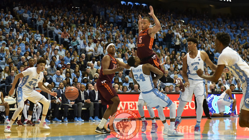 Virginia Tech Hokies guard Justin Robinson (5) goes airborne as North Carolina Tar Heels guard Kenny Williams (24) attempts to draw a charging foul. (Michael Shroyer/ TheKeyPlay.com)