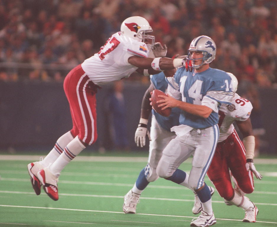 . Arizona Cardinals defensive end Simeon Rice (left, #97) attempts to sack Detroit Lions quarterback Frank Reich (#14) during second half action at the Pontiac Silverdome.