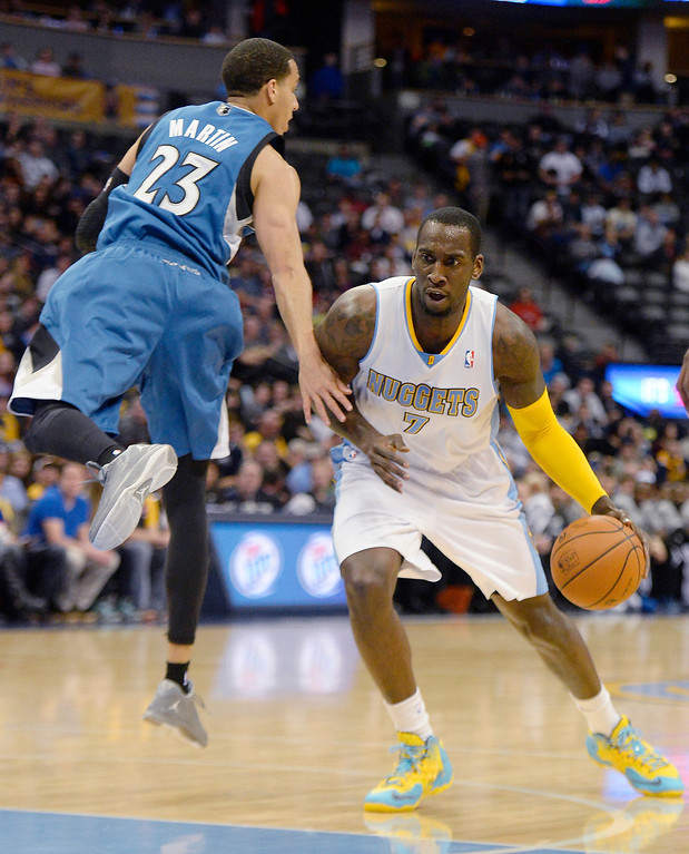 . J.J. Hickson (7) of the Denver Nuggets drives past Kevin Martin (23) of the Minnesota Timberwolves during the first quarter at the Pepsi Center.   (Photo By AAron Ontiveroz/The Denver Post)