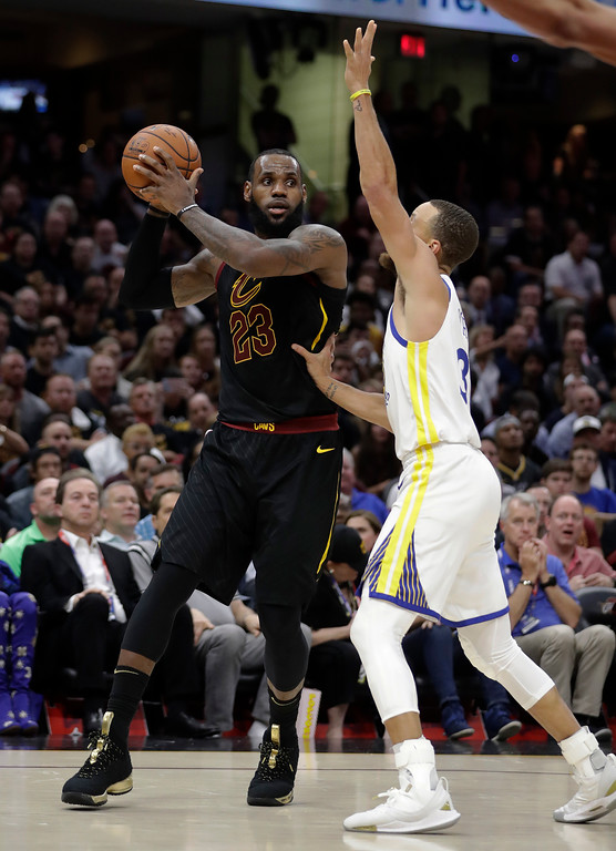 . Cleveland Cavaliers\' LeBron James looks to pass the ball as Golden State Warriors\' Stephen Curry defends during the second half of Game 4 of basketball\'s NBA Finals, Friday, June 8, 2018, in Cleveland. (AP Photo/Tony Dejak)