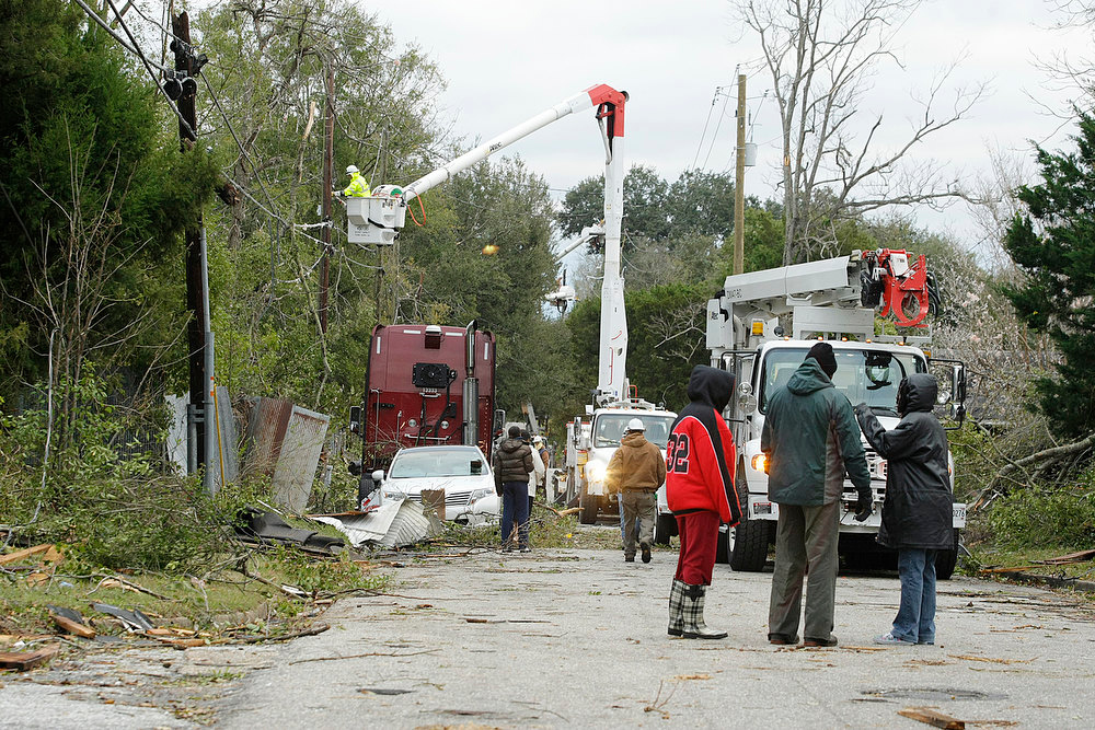 . Utility crews work to restore powe in Mobile, Ala., Wednesday, Dec. 26, 2012, after a tornado swept through the area on Christmas Day. With only a handful of injuries and no deaths reported statewide from the storms, the head of the state\'s emergency response said it was difficult to fathom how the toll wasn\'t worse. (AP Photo/AL.com, Mike Kittrell)