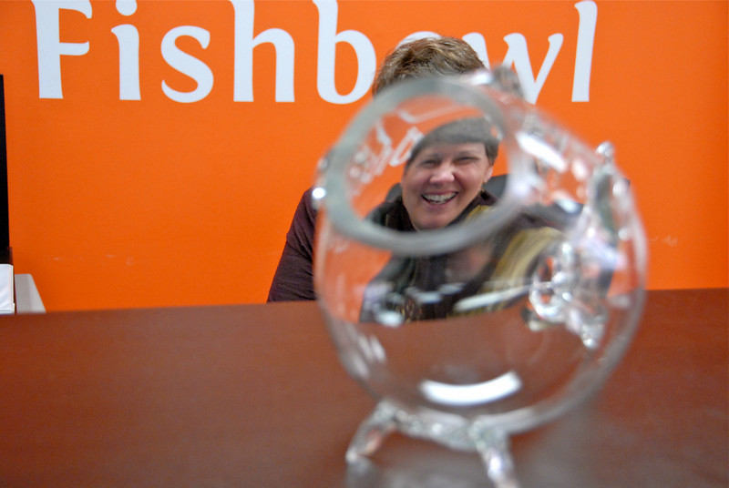 2011/2/9 – Marilyn Bigney sits at our front desk to greet people as they come into the office and to answer the phone. She is also the administrator for our CAM Foundation that provides training, certification and other services for single mothers and other individuals in need. This glass fish sits on the counter at the front desk. I was experimenting shooting her through the open mouth of the fish. It is literally a bowl in the shape of a fish. Kind of a fun touch in the office lobby.