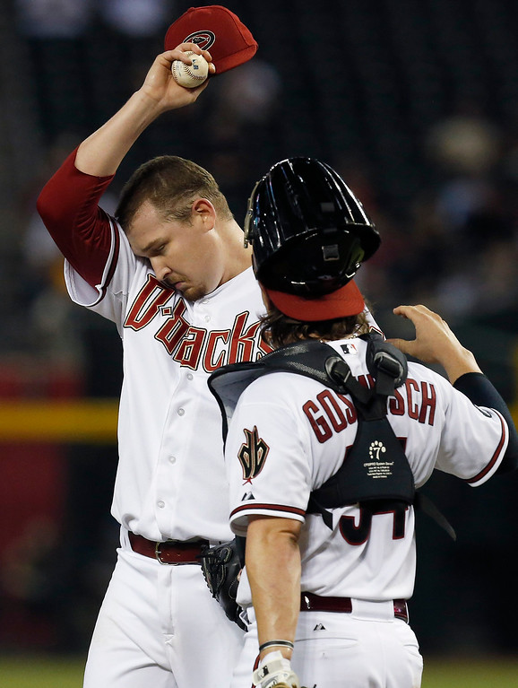 . Arizona Diamondbacks\' Trevor Cahill, left, wipes sweat from his face as he gets a visit from catcher Tuffy Gosewisch in the sixth inning of a baseball game against the Los Angeles Dodgers on Monday, Sept. 16, 2013, in Phoenix.  The Diamondbacks defeated the Dodgers 2-1. (AP Photo/Ross D. Franklin)