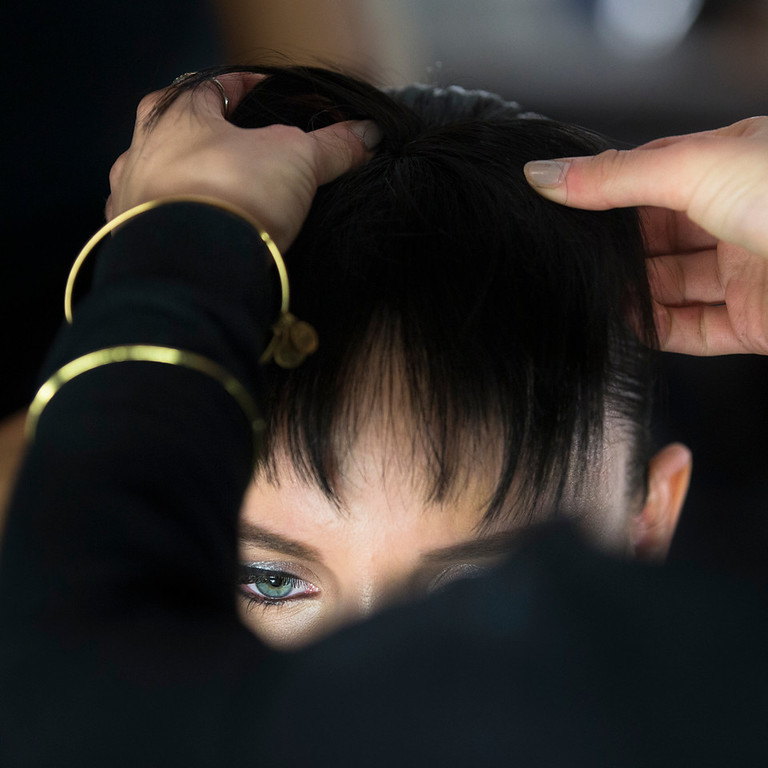 . A model\'s hair is prepared backstage before the Carmen Marc Valvo Fall 2014 collection is modeled during Fashion Week, Friday, Feb. 7, 2014, in New York. (AP Photo/John Minchillo)