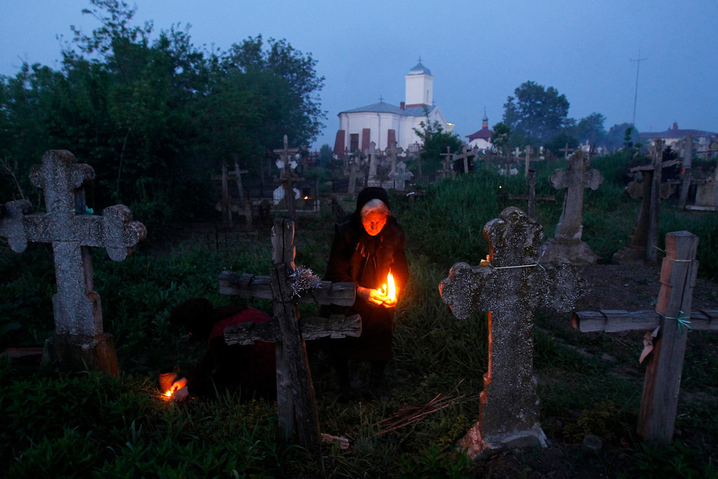. A woman lights a fire in front of the graves of her relatives at a cemetery in the village of Copaciu, 42 km (26 miles) southwest of Bucharest, early morning May 2, 2013. Orthodox women went to church and cemeteries in the early morning on Maundy Thursday to light candles, burn incense and mourn their dead relatives as part of a southern Romania tradition. Maundy Thursday, or Holy Thursday, is the day Christians commemorate the Last Supper of Jesus Christ. Romania\'s Orthodox majority celebrates Easter on May 5. REUTERS/Bogdan Cristel
