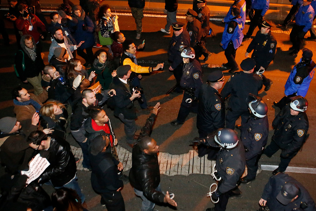 . A group of protesters rallying against a grand jury\'s decision not to indict the police officer involved in the death of Eric Garner confronts police as they are instructed to vacate the eastbound traffic lanes of the Brooklyn Bridge in the early morning hours of Thursday, Dec. 4, 2014, in New York. (AP Photo/Jason DeCrow)