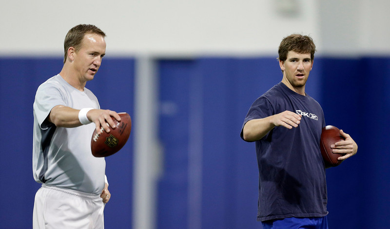 . Denver Broncos quarterback Peyton Manning, left, and brother Eli Manning, quarterback for the New York Giants, talk during football workouts at Duke University in Durham, N.C., Thursday, April 11, 2013. (AP Photo/Gerry Broome)
