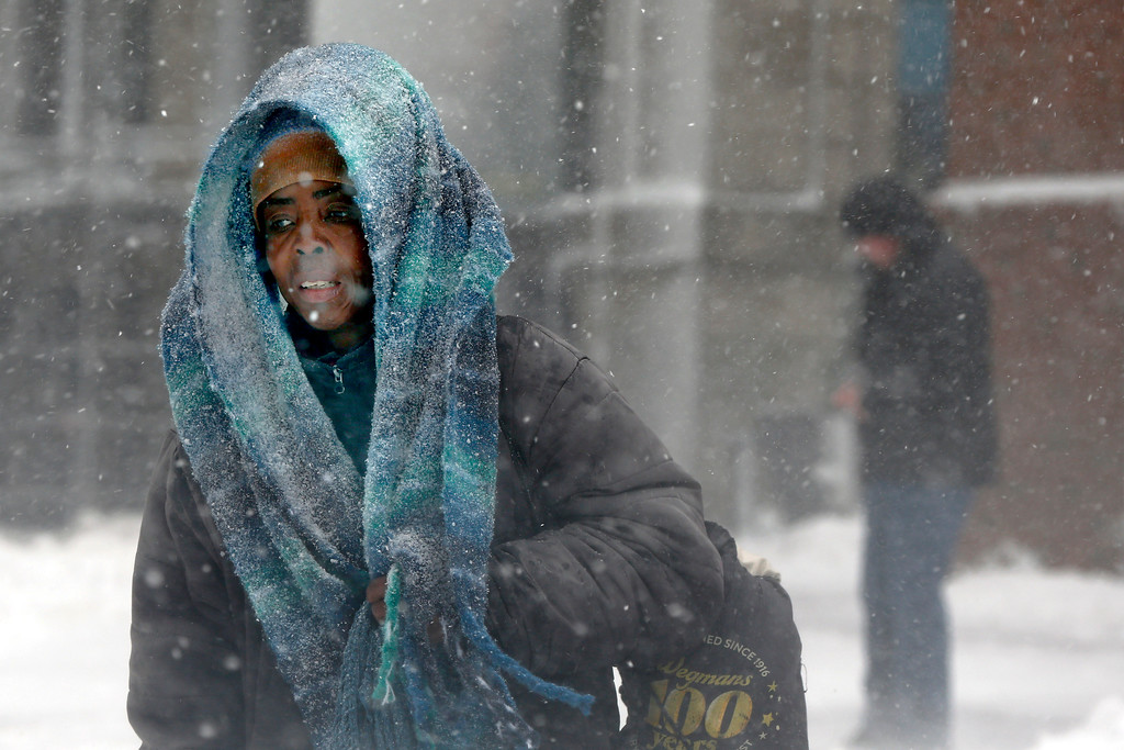 . A woman walks through falling snowflakes during a snowstorm, Tuesday, March 13, 2018, in downtown Boston. (AP Photo/Michael Dwyer)