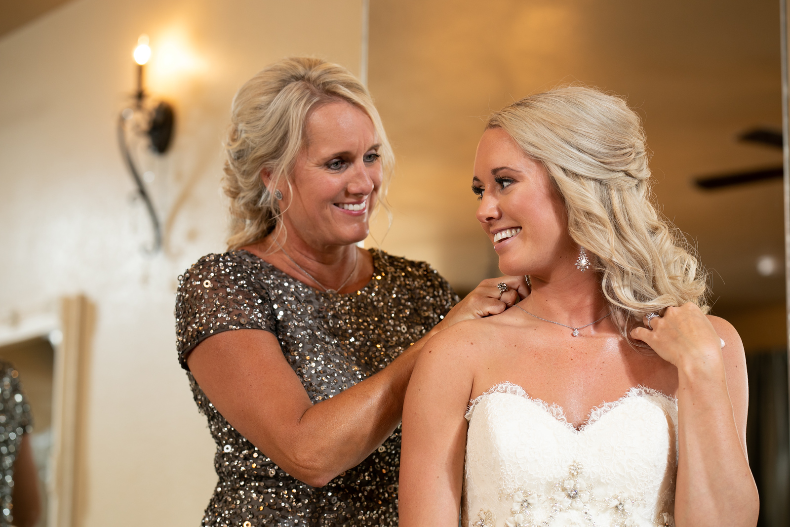 a mom putting a necklace on her daughter just before her wedding