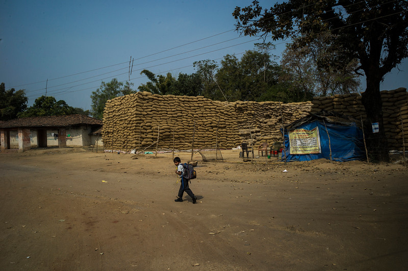 Chattisgarh, India, February 2015:   A school boy walks past the grain collected by the village co-operative. The village is part of the proposed expansion plan.   Photographs for a story on land allocation for coal mines in Chattisgarh.  Modi's new government in the centre has relaxed the environmental regulations so the land can be allocated to both public and private sector companies easily.   Photo by Sami Siva for Al Jazeera America.