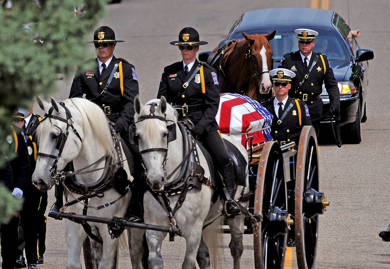 . A caisson and riderless horse, followed by family members, enters Acacia Park Cemetery in Mendota Heights, for the burial of Mendota Heights police officer Scott Patrick Wednesday August 6, 2014.  (Pioneer Press: Jean Pieri)