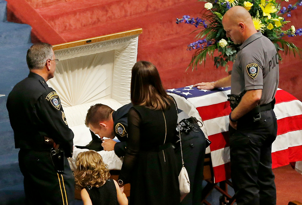 . Oklahoma City police officer Sgt. Ryan Stark, center, leans over the casket of his canine partner, K-9 Kye, following funeral services for the dog in Oklahoma City, Thursday, Aug. 28, 2014. K-9 Kye, a three year old Belgian German Shepard, died Aug. 25 after being stabbed by a burglary suspect on Aug. 24. Sgt. Stark tried to separate the dog and the suspect before fatally shooting the suspect. (AP Photo/Sue Ogrocki)