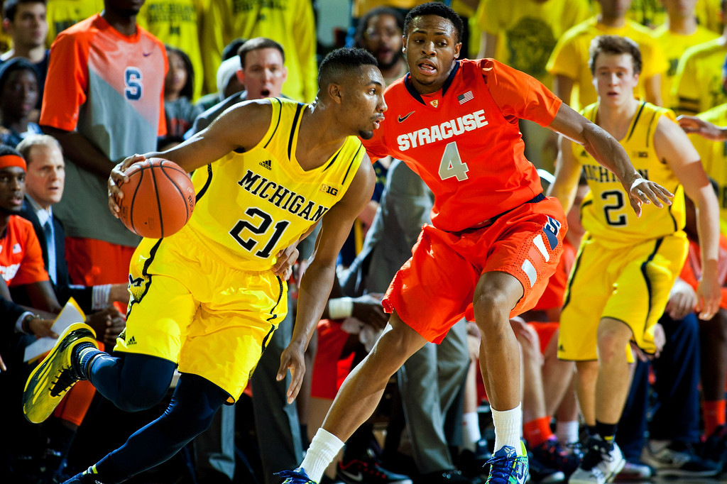 . Michigan guard Zak Irvin (21) drives against Syracuse guard Ron Patterson (4), in the first half of an NCAA college basketball game at Crisler Center in Ann Arbor, Mich., Tuesday, Dec. 2, 2014. (AP Photo/Tony Ding)