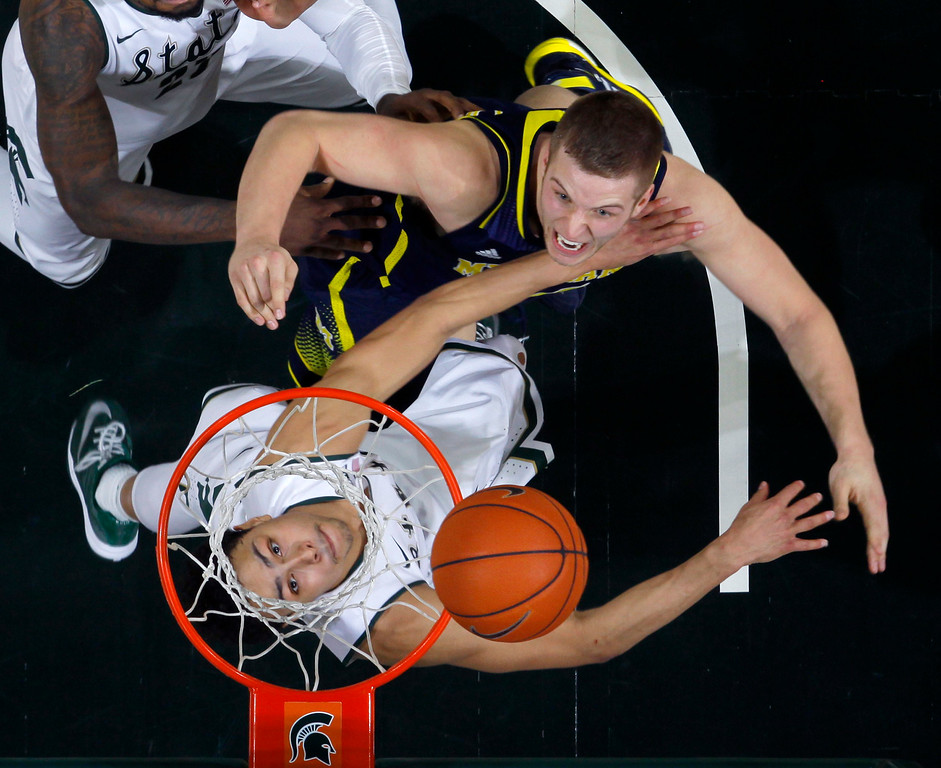 . Michigan State\'s Bryn Forbes, left, and Michigan\'s Max Bielfeldt battle for a rebound during overtime of an NCAA college basketball game, Sunday, Feb. 1, 2015, in East Lansing, Mich. Michigan State won 76-66 in overtime. (AP Photo/Al Goldis)