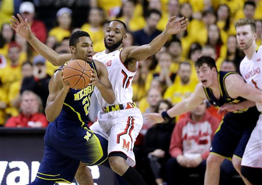. Michigan guard/forward Zak Irvin, left, looks for a teammate as he is pressured by Maryland guard/forward Dez Wells in the second half of an NCAA college basketball game, Saturday, Feb. 28, 2015, in College Park, Md. Maryland won 66-56, despite 15 points from Irvin. (AP Photo/Patrick Semansky)