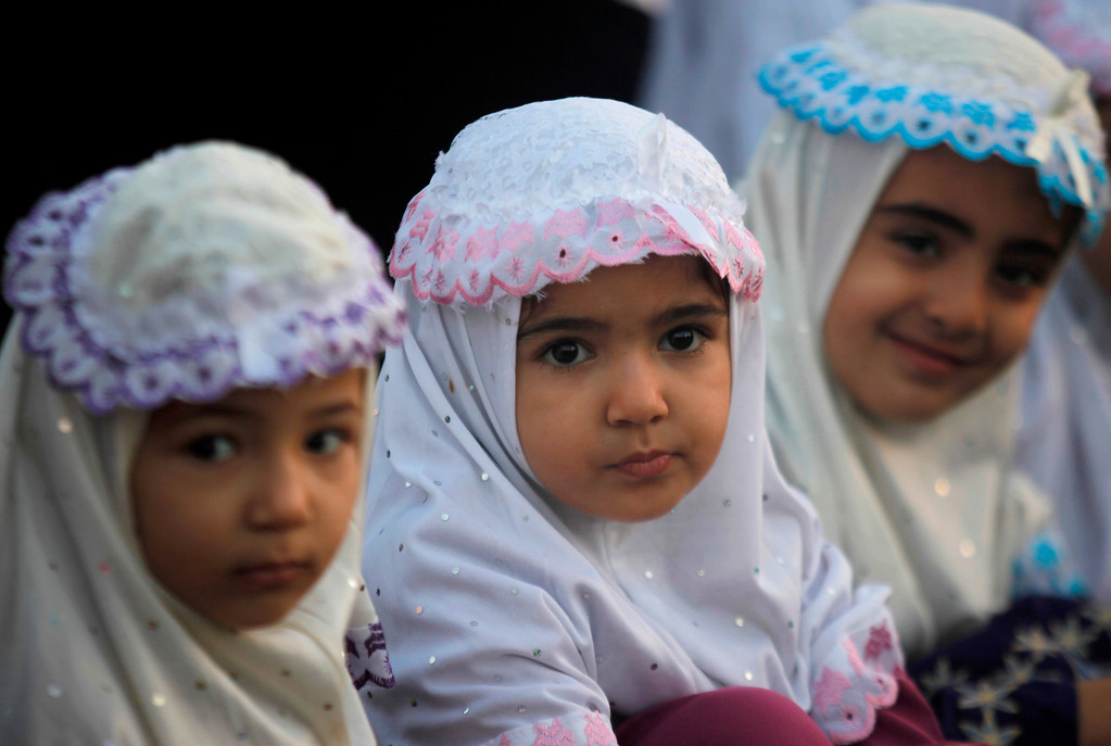 . Palestinian girls attend prayers on the first day of Eid al-Adha in Al-Yarmouk stadium in Gaza City, Tuesday, Oct. 15, 2013.   (AP Photo/Hatem Moussa)