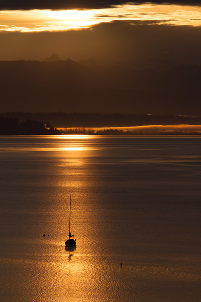 Sunrise morning rays are reflected in Puget Sound as the sun rise over teh Cascade Mountains with a sailboat moored in the foreground