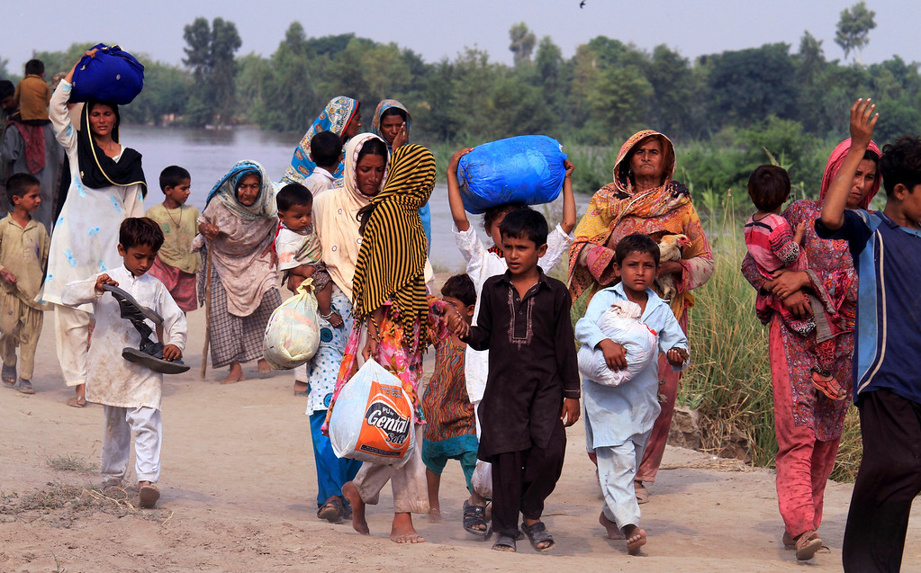 . Villagers evacuate their homes along the Chenab River, in Jhang, Pakistan, Wednesday, Sept. 10, 2014. (AP Photo/K.M. Chaudary)