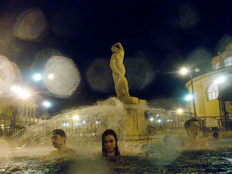 March , 2012, Budapest, Hungary -  Tourists enjoy hot bath in one of three outdoor pools in Szechenyi Bath, where locals and tourists spend as long as 10 hrs a day in the water.   Budapest is known as the SPA Capital of the world.  Nearly 120 hot springs feed the city's historic thermal baths (Furdo) and approximately 70 million litres of water used every day. The water full of minerals is supposed to cure many illness.