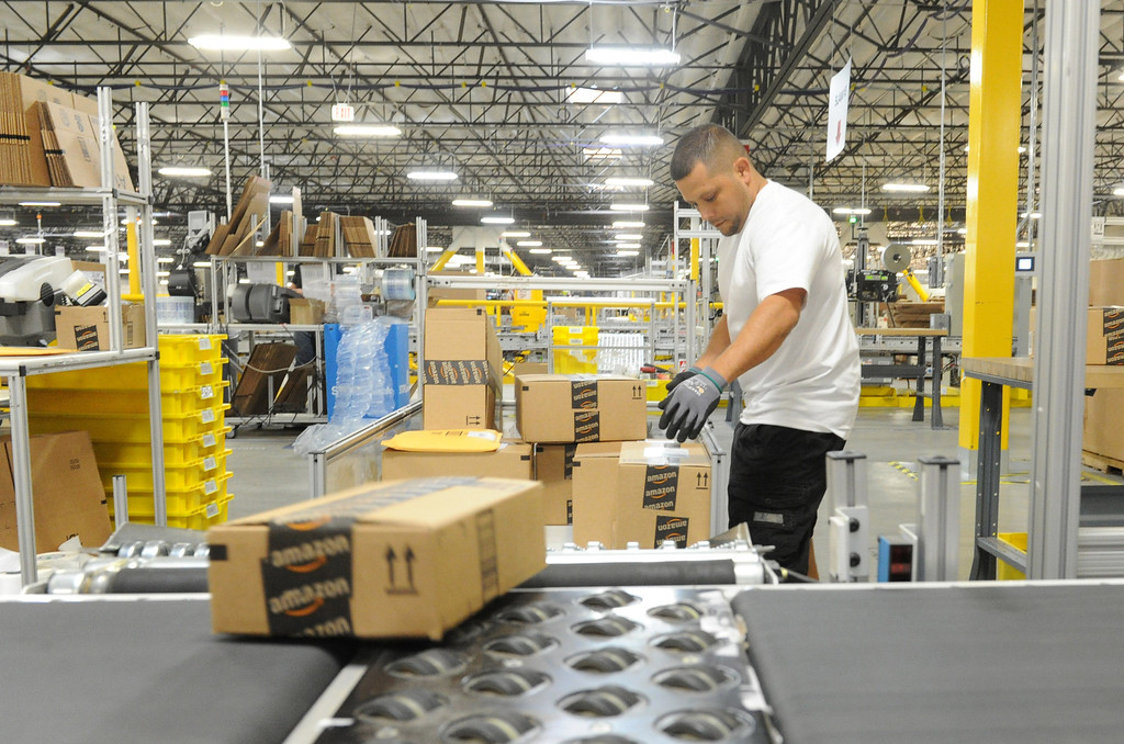 . Amazon\'s Slam operator Steve Morgan sorts through merchandise at the The Amazon Fulfillment Center in San Bernardino, CA., Monday, Oct. 28, 2013. The fulfillment center opened up a year ago with only half of the facility opened for business, now with the the million-square-foot center complete they will host a grand opening on Tuesday, with Gov. Jerry Brown in attendance.  This distribution center has been celebrated in San Bernardino and at the state level as an example of job creation and growth. (John Valenzuela/Staff Photographer)