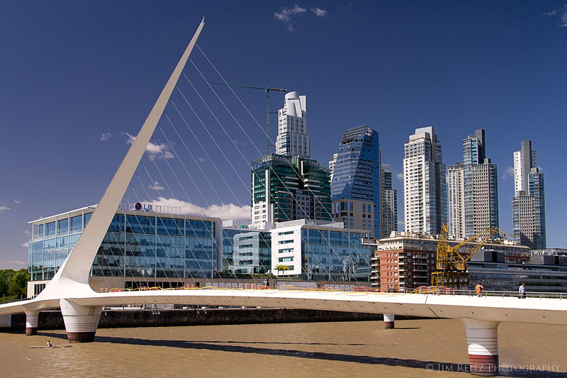 "Puente de la Mujer - ""Women's Bridge"" - in Buenos Aires, designed by Spanish architect Santiago Calatrava. The ultra-modern district of Puerto Madero rises in the background."