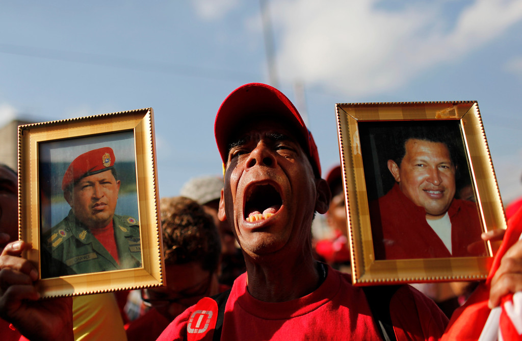 . A supporter of Venezuela\'s late President Hugo Chavez holds images of him while the coffin containing his body passes in the street, from the hospital where he died on Tuesday to a military academy where it will remain until his funeral in Caracas, Venezuela, Wednesday, March 6, 2013.  (AP Photo/Rodrigo Abd)