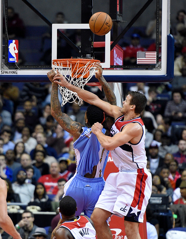 . Washington Wizards forward Kris Humphries, right, fouls Denver Nuggets forward Wilson Chandler, left, during the second half of an NBA basketball game, Friday, Dec. 5, 2014, in Washington. (AP Photo/Nick Wass)