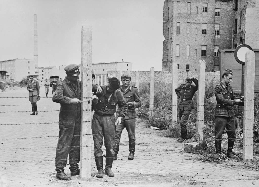 . Soldiers of the East German National People\'s Army (NVA) erecting barbed wire fences to close off a street in preparation for the construction of the Berlin Wall, Berlin, Germany, 14th August 1961. The first concrete emplacements were erected on 17th August. (Photo by Keystone/Hulton Archive/Getty Images)