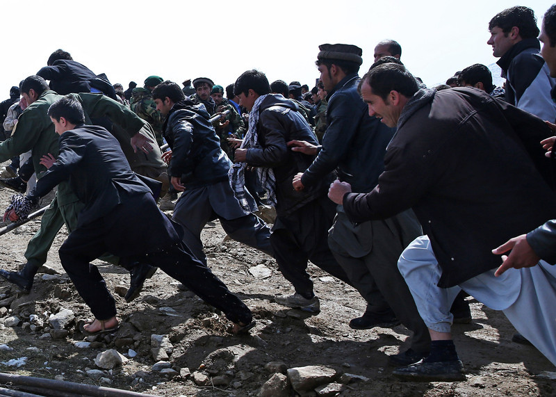 . Afghan men run to to get a better view as they attend in the burial of Afghanistan\'s influential Vice President Mohammad Qasim Fahim during his funeral in Kabul, Afghanistan, Tuesday, March 11, 2014.  (AP Photo/Massoud Hossaini)