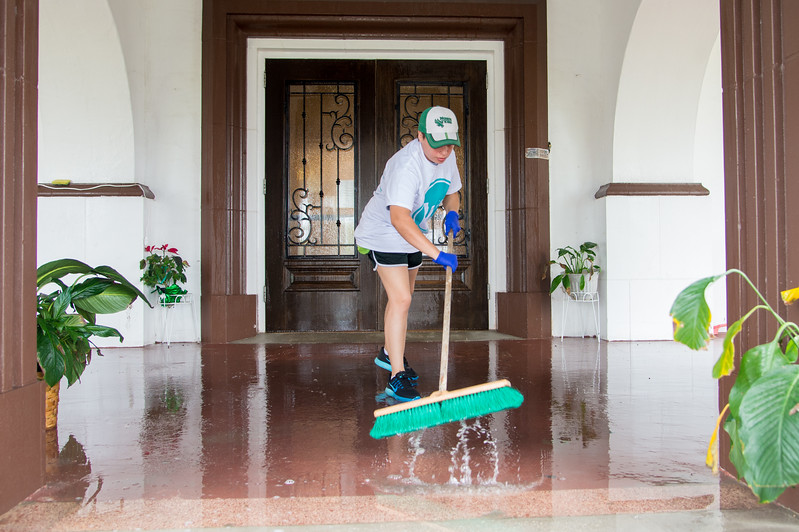 Student volunteer Brooke Yrigoyen washing the front patio of Mt. Carmel Home.