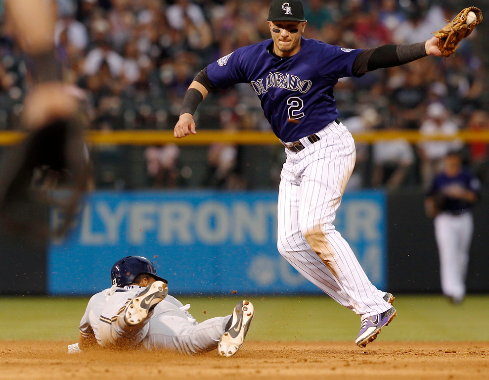 . Milwaukee Brewers\' Carlos Gomez, left, steals second base as Colorado Rockies shortstop Troy Tulowitzki fields the throw in the fifth inning of a baseball game in Denver on Saturday, July 27, 2013. (AP Photo/David Zalubowski)