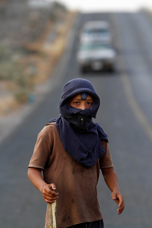 . In this May 20, 2013 photo, a masked youth stands guard at the entrance of the town of Buenavista, Mexico.  Self-defense groups started to spring up in February to fight back the Knights Templar drug cartel which is extorting protection payments from cattlemen and lime growers, butchers and even marijuana growers. The federal government sees both the self-defense forces and the cartel as dangerous enemies. (AP Photo/Marco Ugarte)