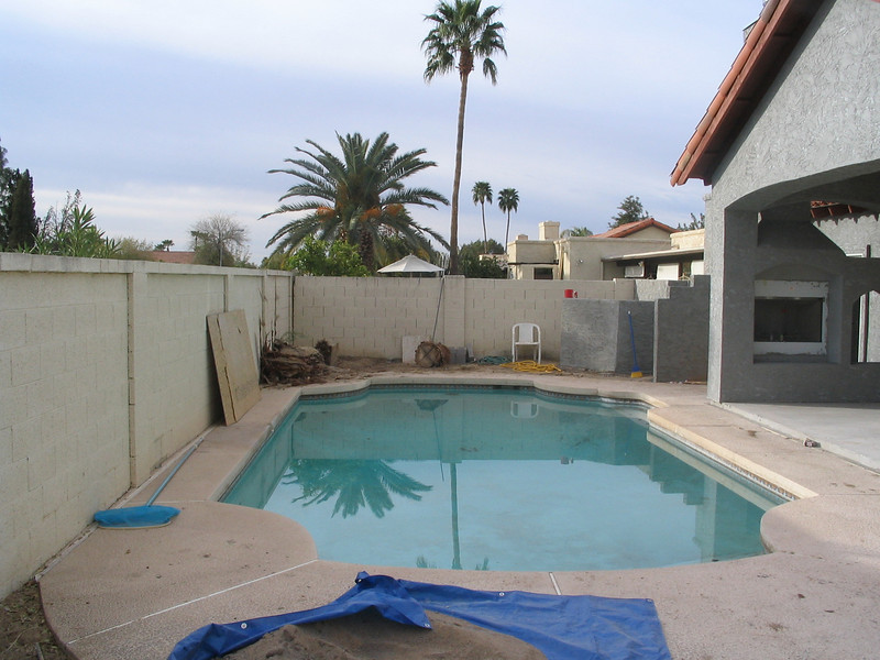 The back yard and pool, with our new covered patio and the finished walls.